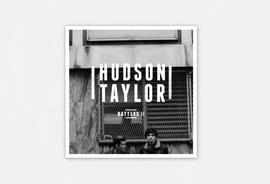 Black And White Two Men In Front Of Metal Shutters With Logo And Song Name