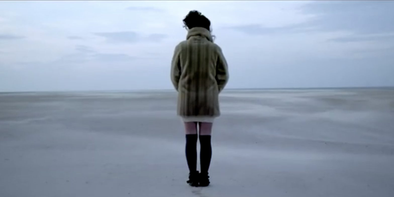 Female Singer In Fur Coat Standing On Sandy Beach With Ocean Background