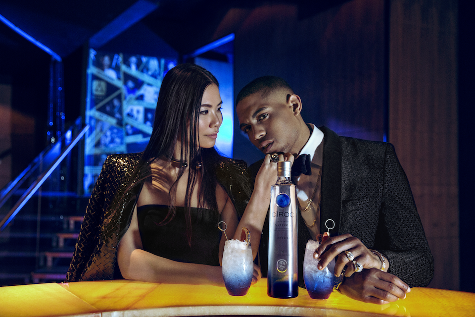 Male And Female Model Sitting At Bar In London Club Styled In High Fashion Drinking Ciroc Vodka