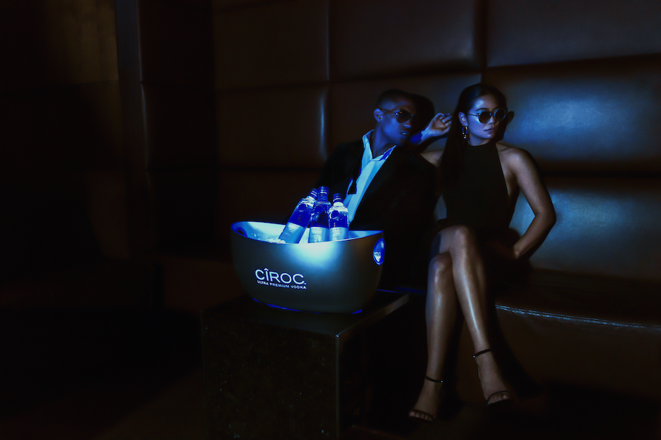Male And Female Model Sitting In London Club VIP Lounge Styled In High Fashion Drinking Ciroc Vodka