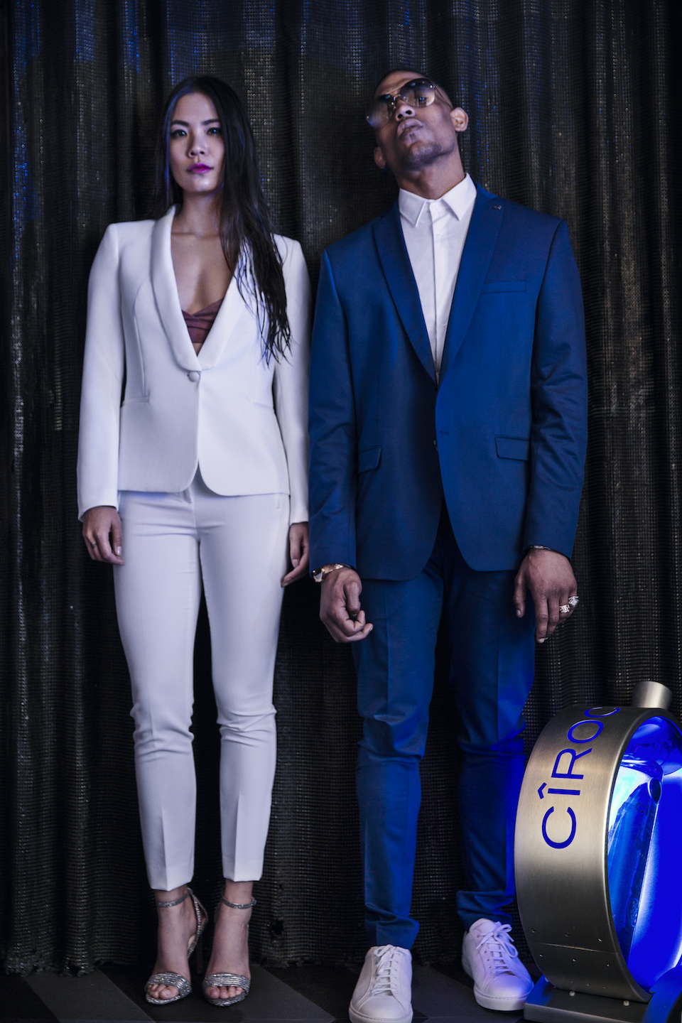 Male And Female Model Standing In London Club Styled In High Fashion Next To Ciroc Vodka Bottle