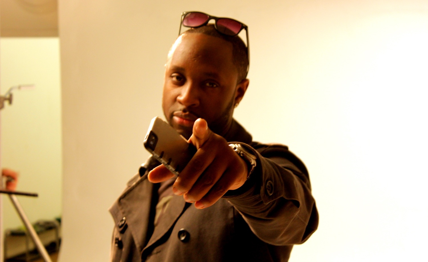Professional Photography Closeup Of Black Man In Khaki Jacket Wearing Sunglasses Holding Phone Pointing To Camera On White Studio Backdrop