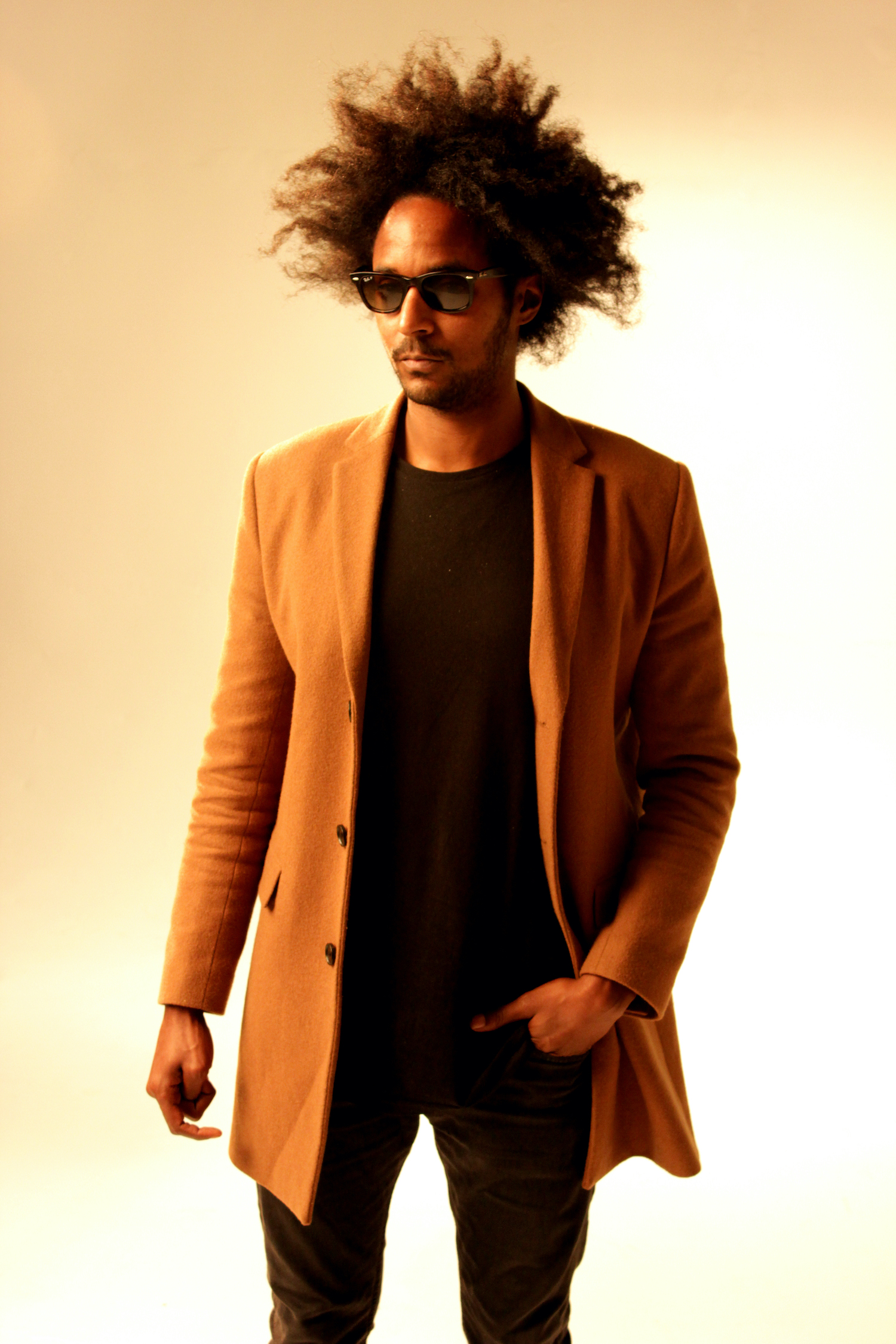 Professional Photography Black Man In Black Shirt Jeans Sunglasses And Orange Blazer Standing On White Studio Backdrop