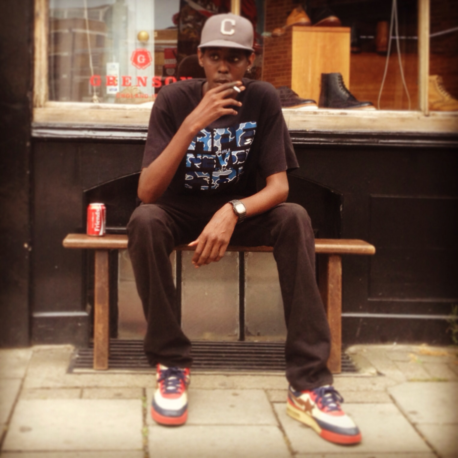 Professional Photography Black Man Sitting On Bench Sitting Outside Grenson Shoe Shop In Brick Lane London