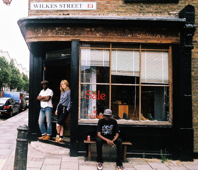 Professional Photography Black Man Sitting Outside Of Grenson Shoe Store Wearing Bathing Ape With Two People In Doorway In Brick Lane Wilkes Street