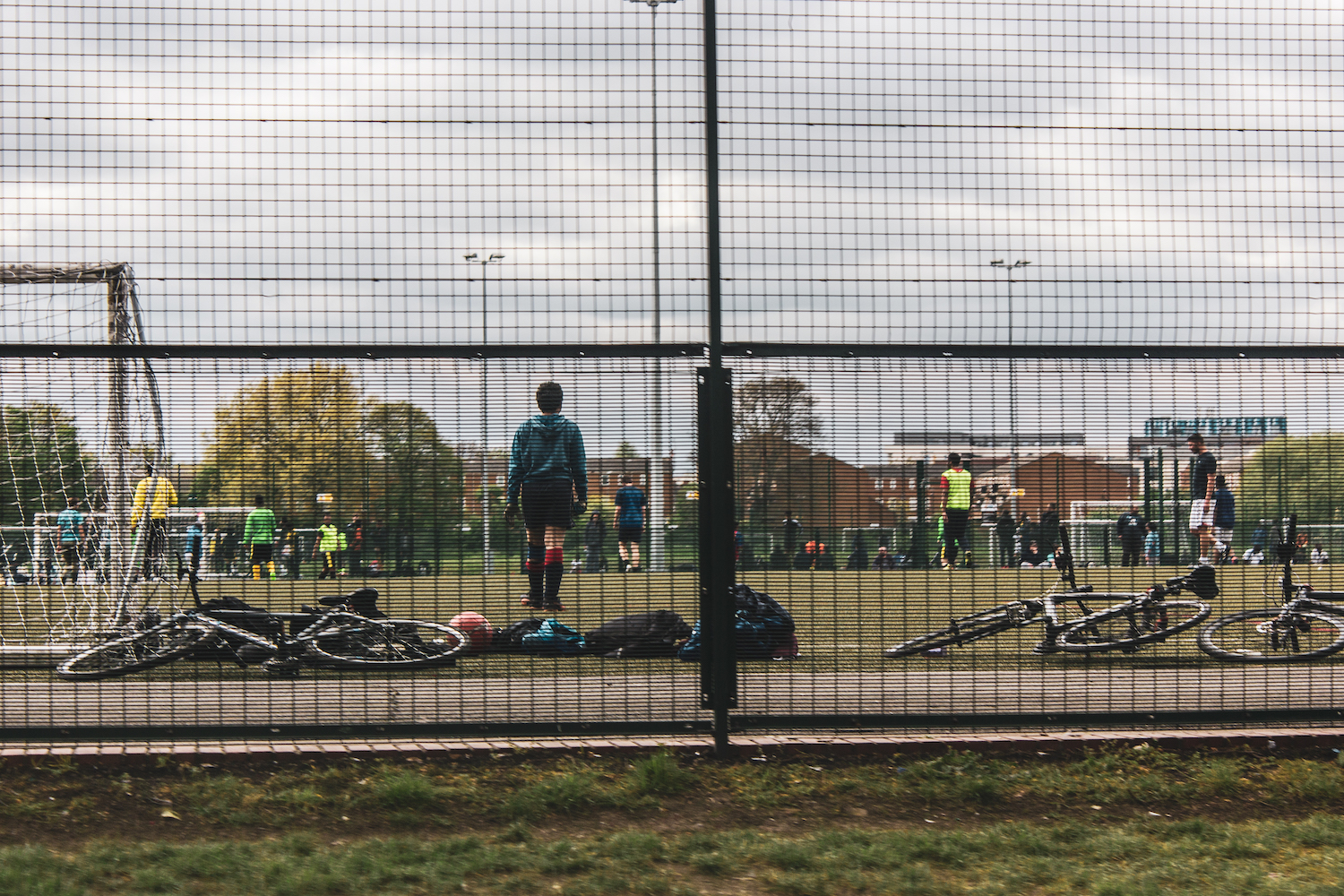 Professional Photography Male Goalkeeper Behind Fence On Football Pitch Playing A Game