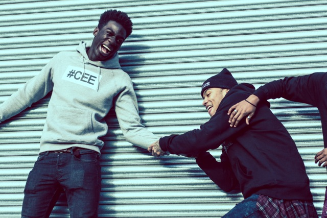 Professional Photography Black Man Wearing Grey Hashtagcee Hoodie Being Pulled By Man Wearing Black Hashtagcee Generals Hoody In Front Of Grey Shutters