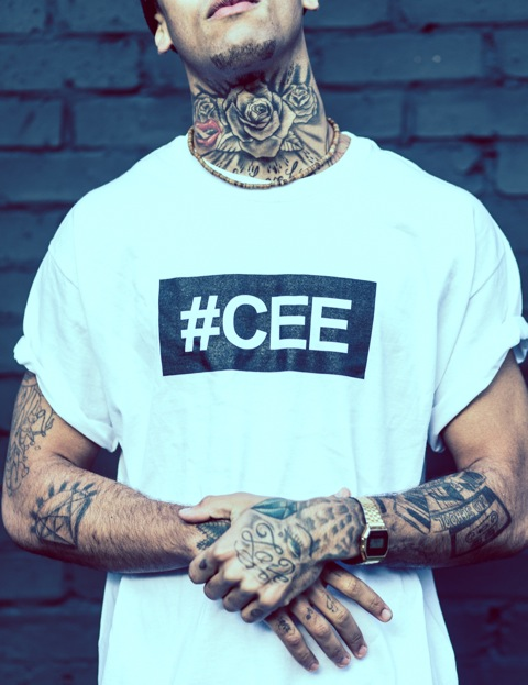 Professional Photography Close-Up Of Black Man With Tattoos In Front Of Black Brick Wall Wearing White Hashtagcee Generals T-Shirt