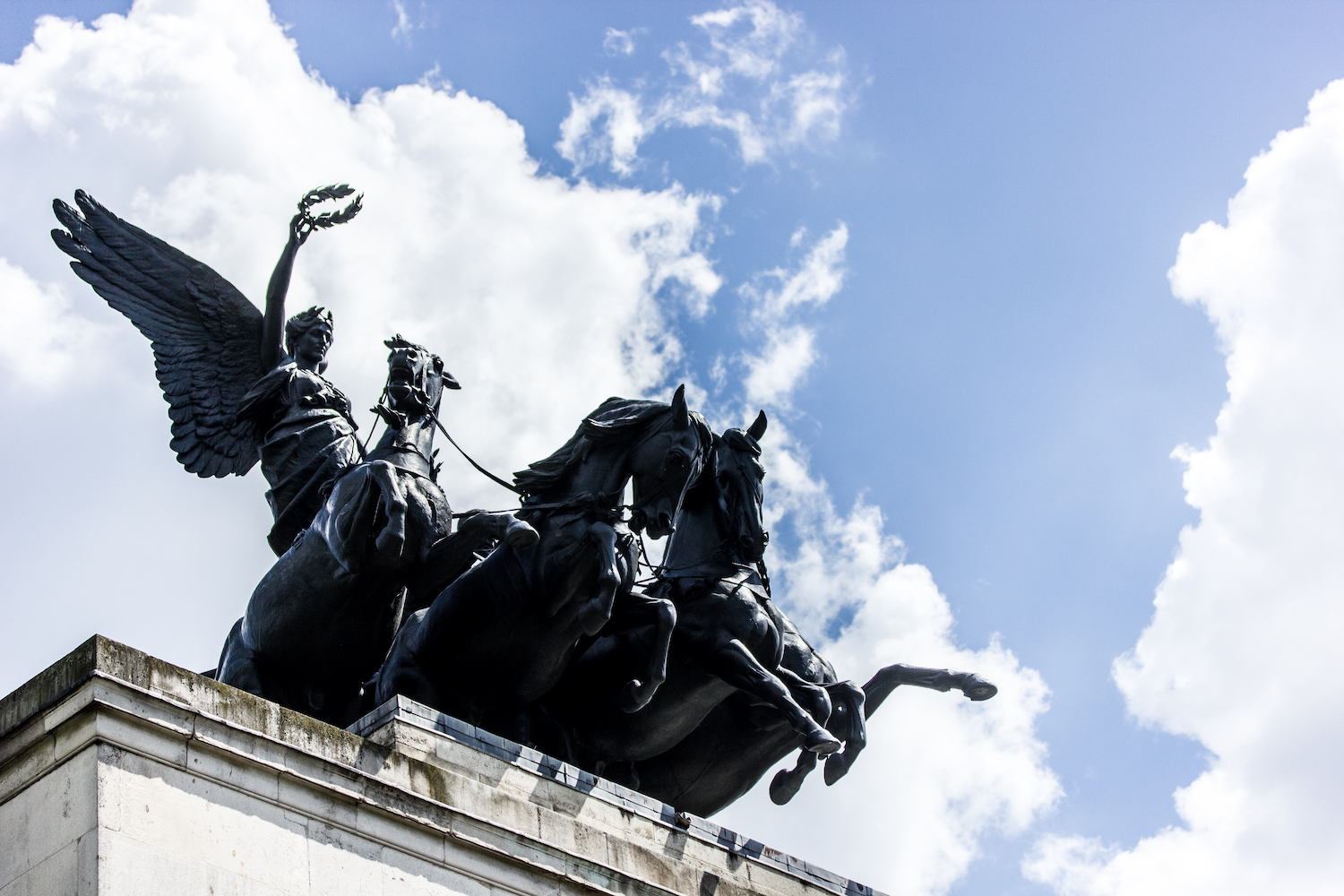 Professional Photography Black Statue Of Woman On Chariots With Three Horses On Top Of Arch With Blue Sky And Clouds At Hyde Park London