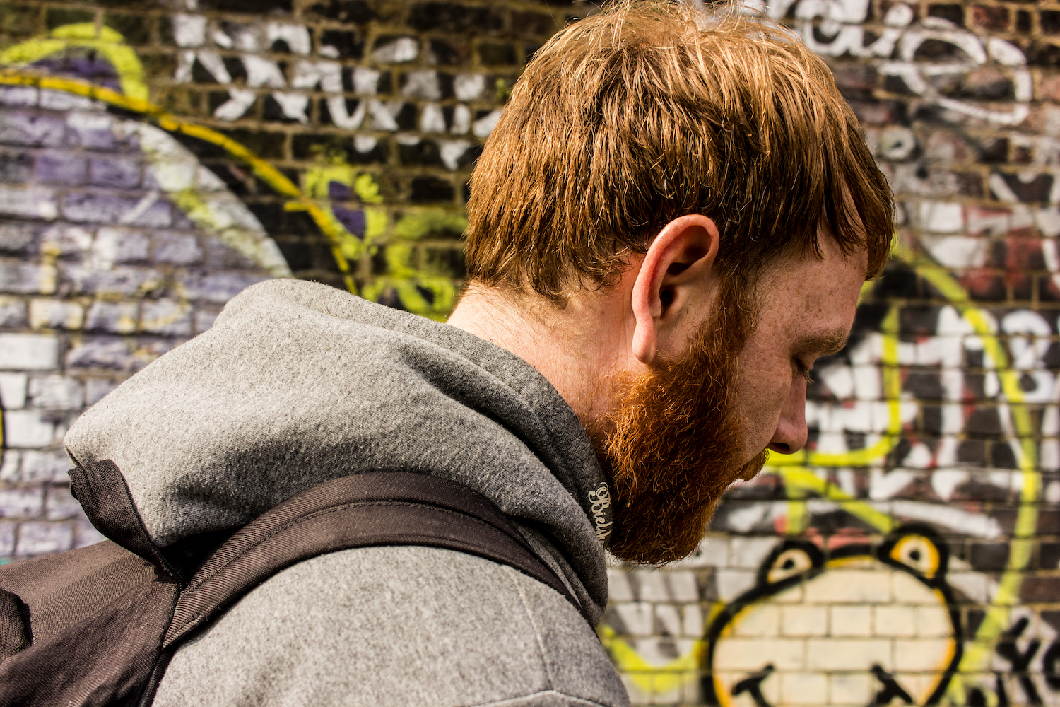 Professional Photography White Man With Beard Grey Hoodie And Black Backpack Walking In Front Of Graffiti Wall