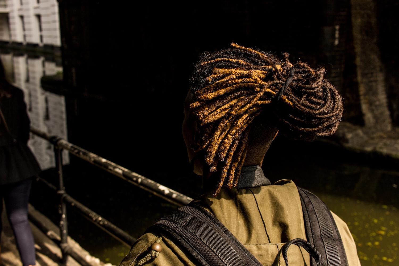 Professional Photography Black Woman With Khaki Jacket Black Backpack And Dreadlocks Walking Under Bridge In Little Venice Paddington London