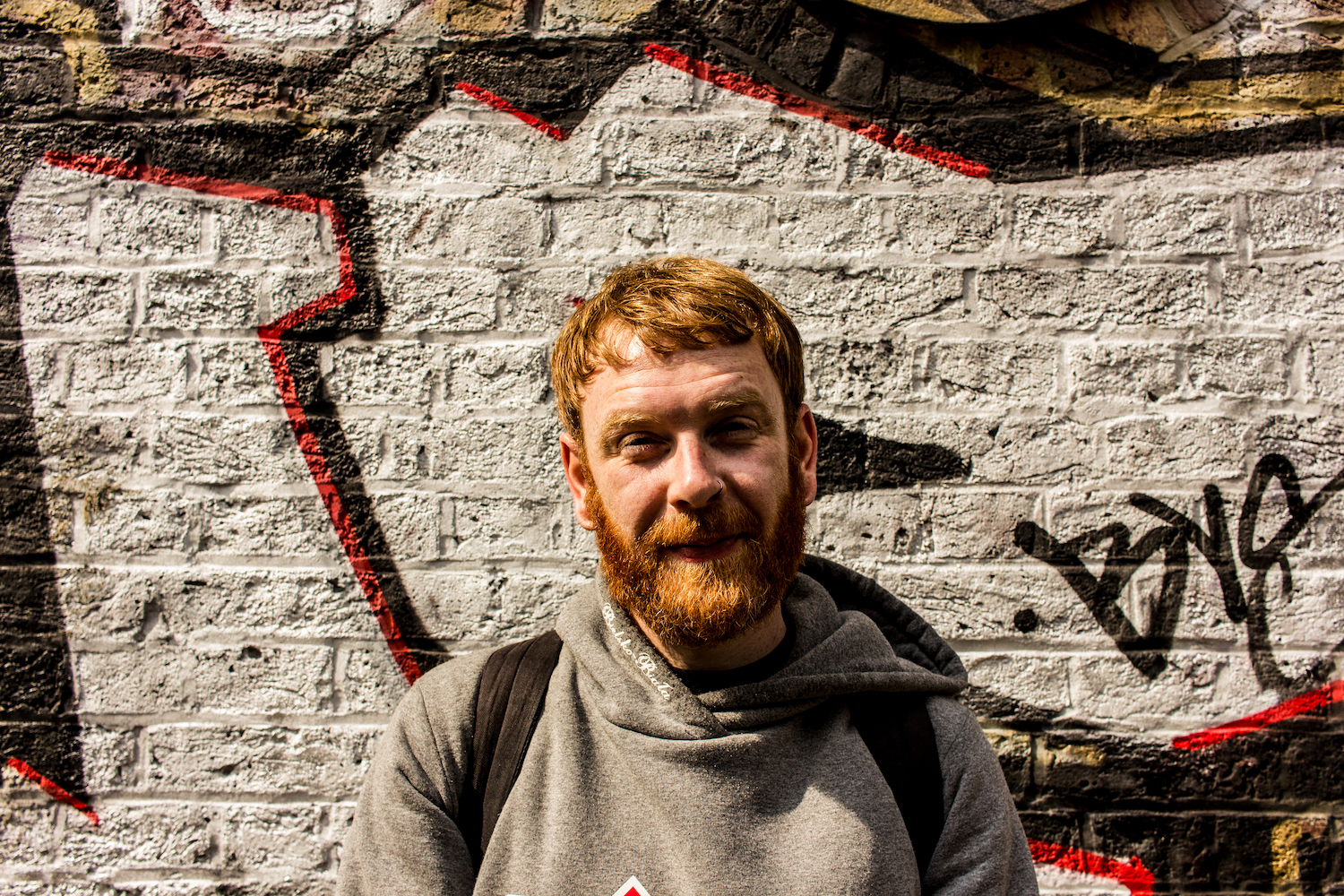 Professional Photography White Man With Beard Grey Hoody And Black Backpack Standing In front of Graffiti Wall