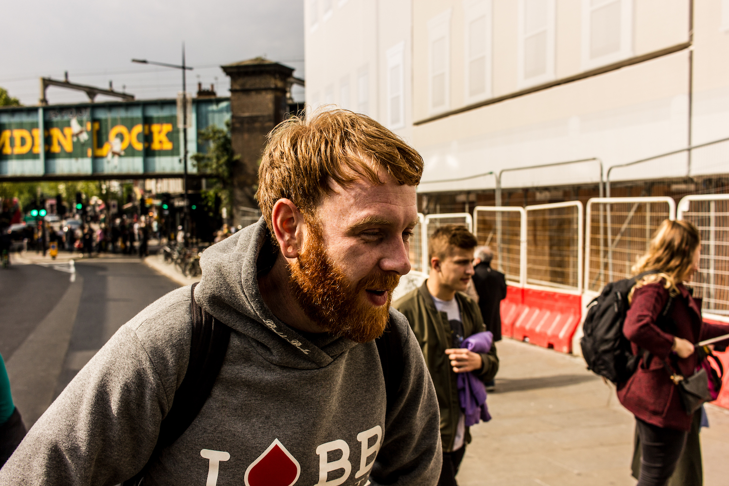 Professional Photography White Man With Beard In Grey Hoody Black Jeans And Backpack Exhausted In Front Of Bridge In Camden Town