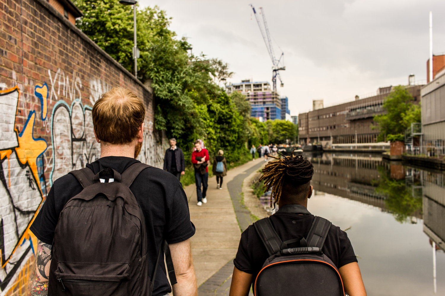Professional Photography White Man With Beard Black T-Shirt And Black Backpack Walking With Dreadlocks Black Woman Carrying Black Backpack Walking Alongside River Canal In Camden With Graffiti Crane And Buildings In Background