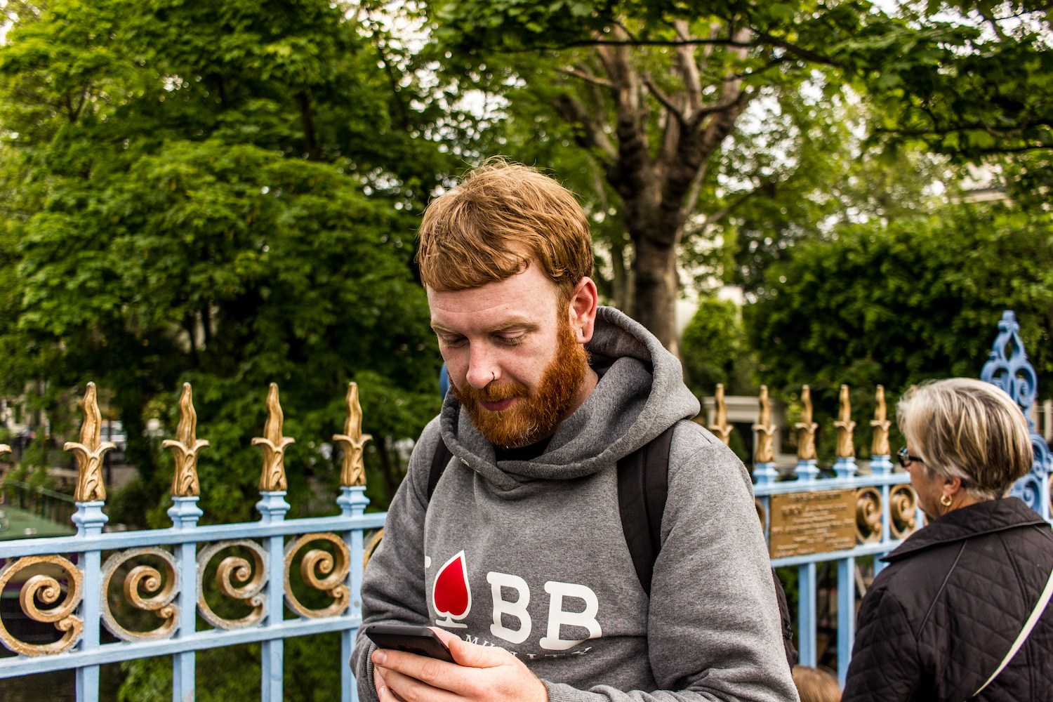 Professional Photography White Man Beginning Ten Mile Charity Walk Wearing Grey Hoody Standing Looking At Phone With Green Trees In Little Venice Paddington London