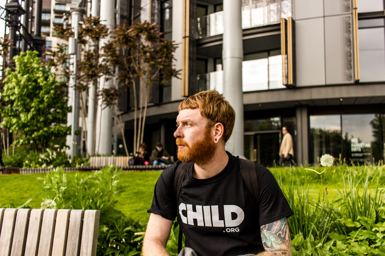Professional Photography White Man With Beard Wearing Black Child.org T-Shirt Sitting On Bench In Front Of Bushes And Metal Buildings In Camden London