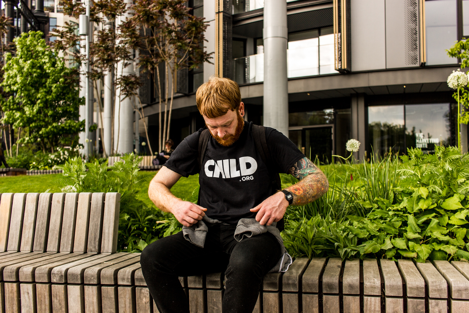 Professional Photography White Man With Beard Showing Black Child.org T-Shirt Sitting On Bench In Front Of Bushes And Metal Buildings In Camden London