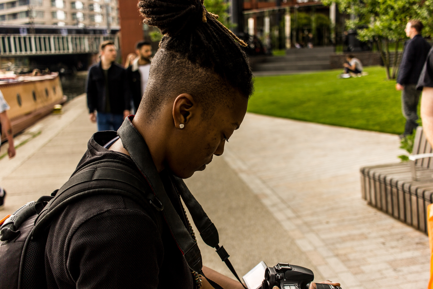 Professional Photography Black Woman Wearing Black T-Shirt With Black Backpack And Dreadlocks Filming With Camera Green Grass And People In Background Camden London