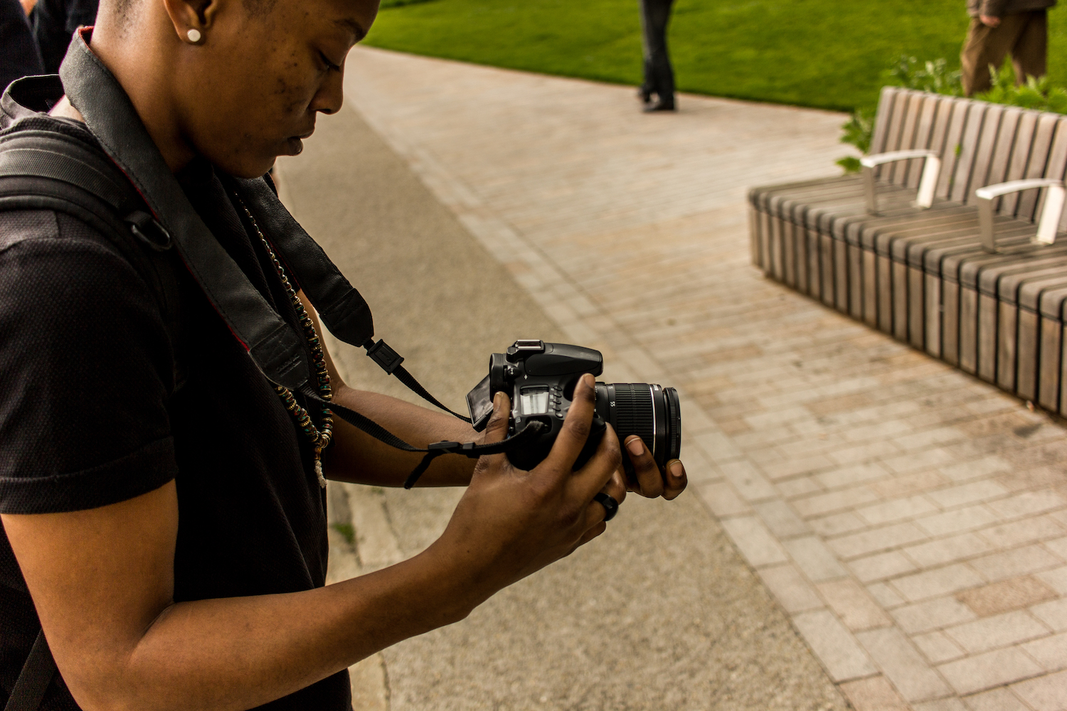 Professional Photography Close-Up Of Black Woman Wearing Black T-Shirt With Black Backpack And Dreadlocks Filming With Camera Green Grass In Background Camden London