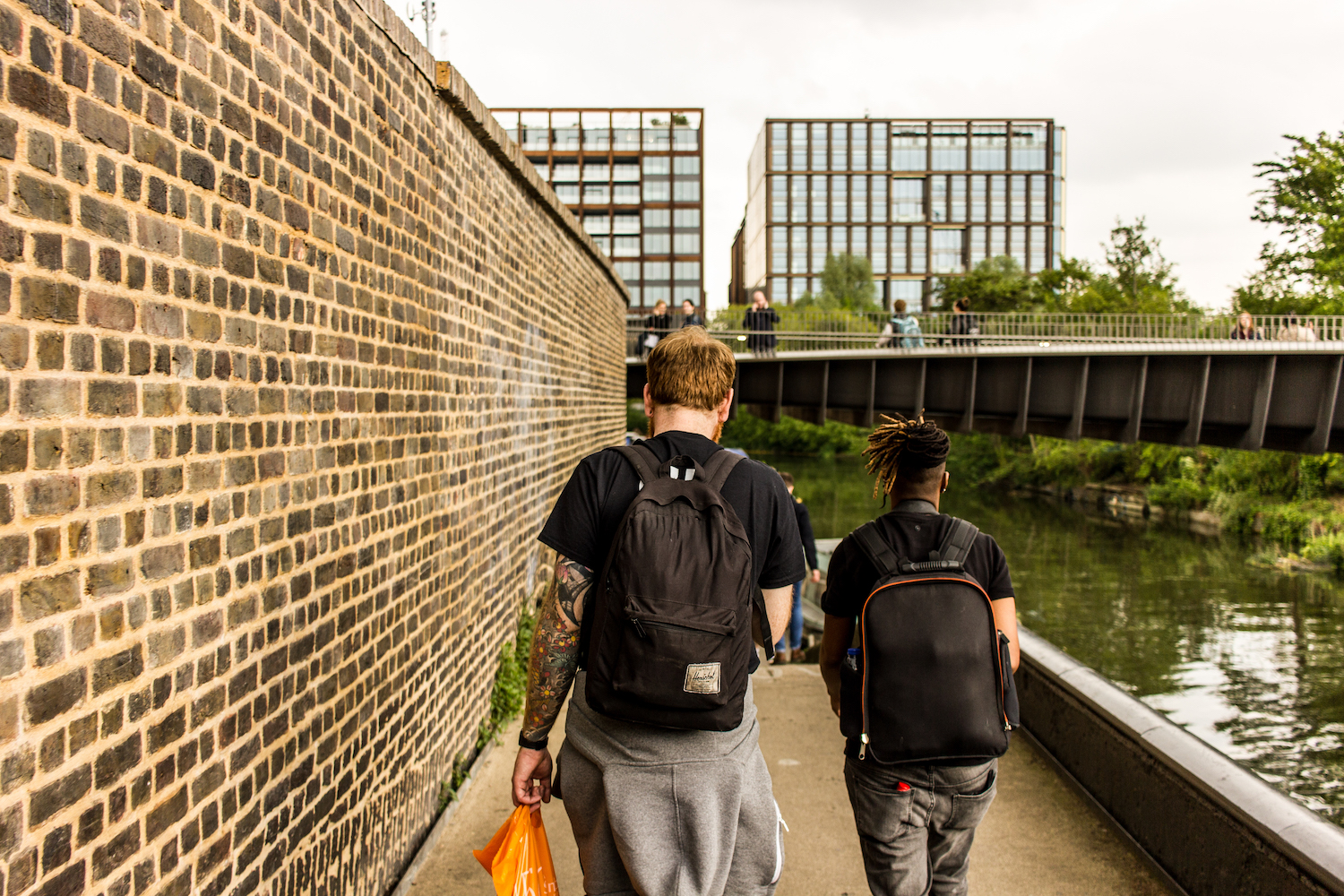 Professional Photography White Man With Beard Black T-Shirt And Black Backpack Walking With Dreadlocks Black Woman Wearing Black T-Shirt And Black Backpack Walking Alongside River Canal To Limehouse Basin