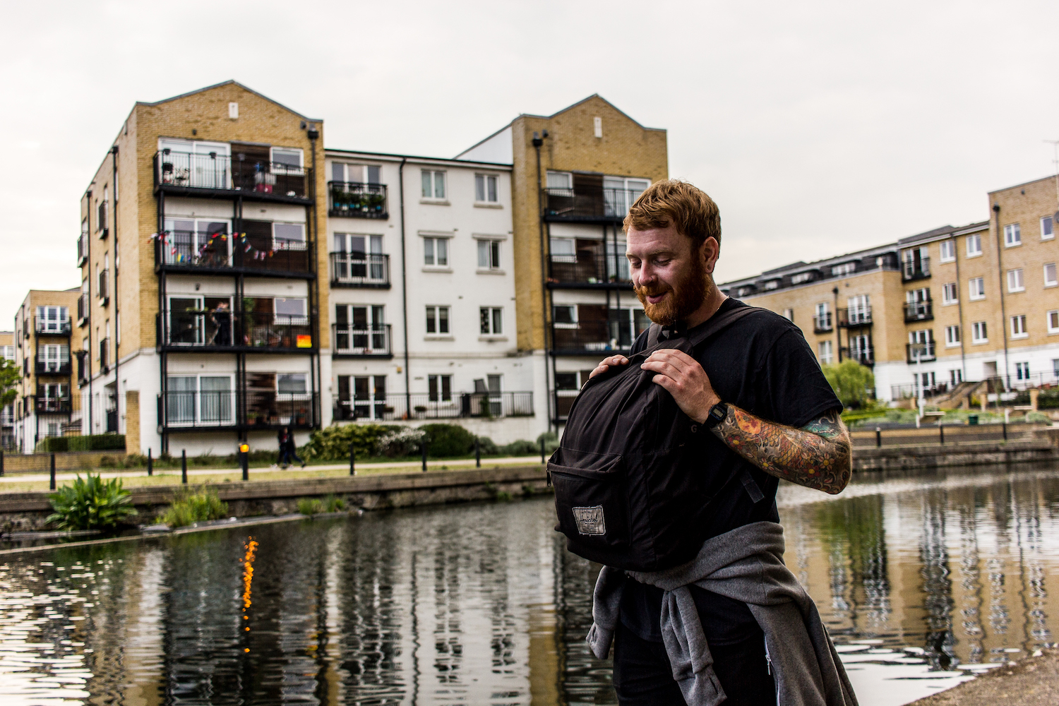 Professional Photography White Man With Beard Wearing Black T-Shirt Grey Hoody Around Waist Holding Black Backpack Over Stomach In Front Of River Canal With Buildings In Background