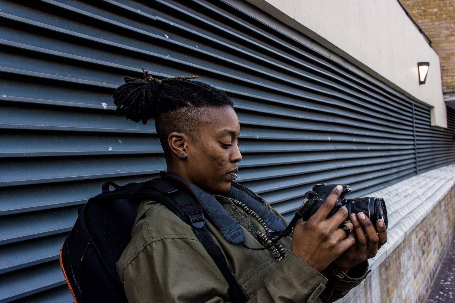 Professional Photography Black Woman With Lip Ring Khaki Jacket Black Backpack And Dreadlocks Leaning Against Wall With Vents Filming With Camera In Limehouse Basin