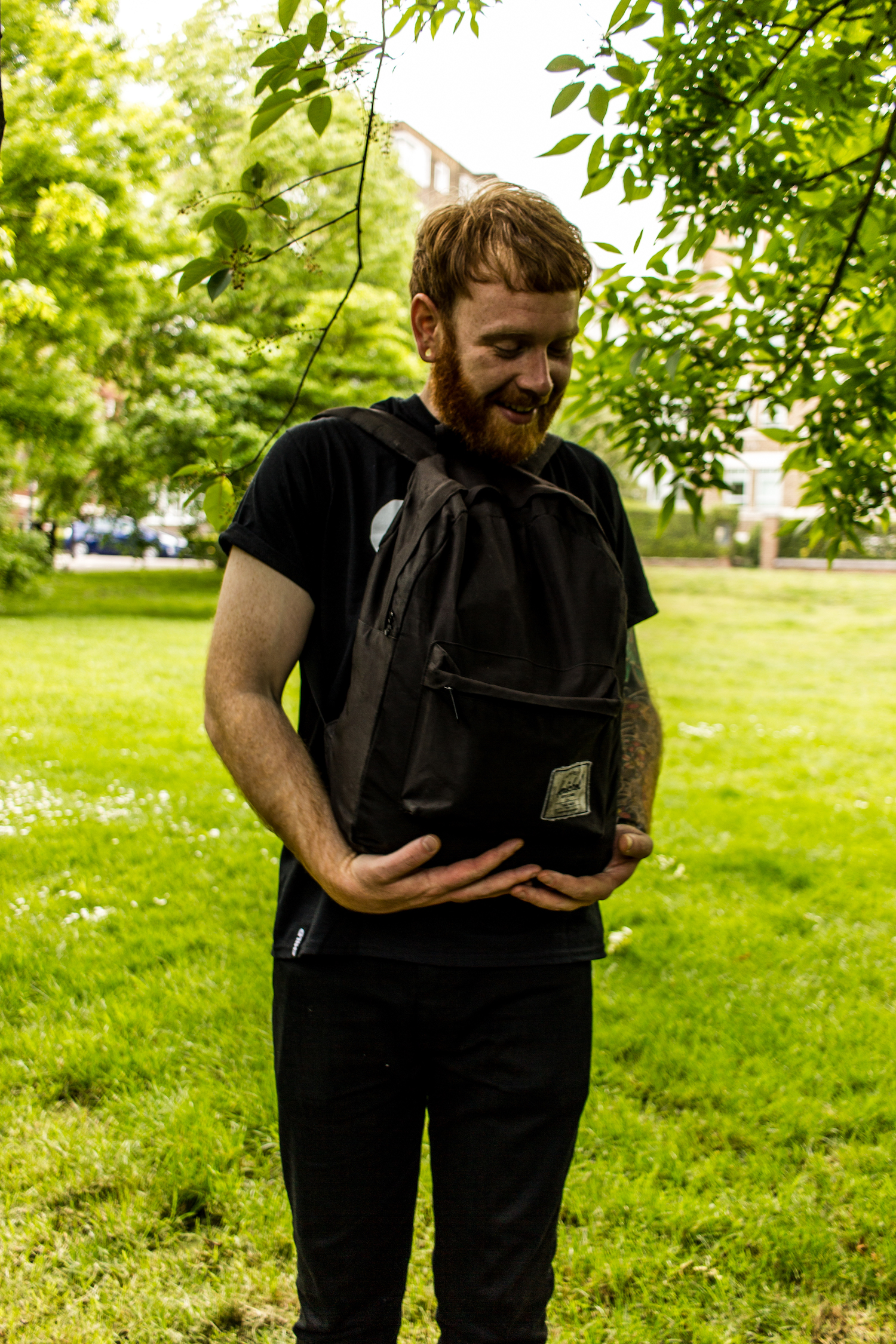 Professional Photography White Man With Beard Black T-Shirt And Black Jeans Standing Holding Black Backpack With Green Grass And Trees In Background In Little Venice Paddington London