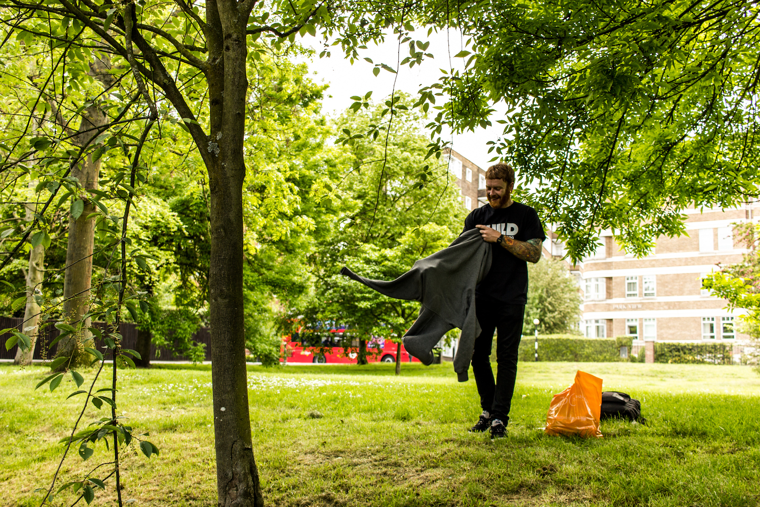 Professional Photography White Man With Beard Black T-Shirt And Black Jeans Holding Grey Hoody With Green Grass Trees And Buildings In Background In Little Venice Paddington London