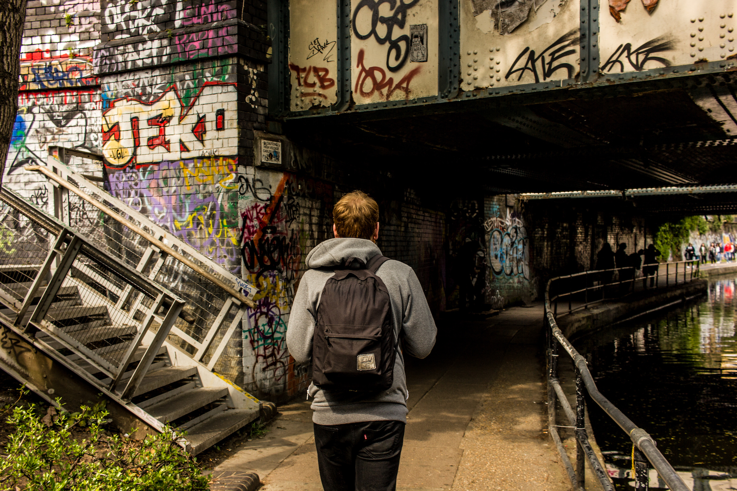 Professional Photography White Man In Grey Hoody Black Jeans And Backpack Walking Under Bridge With Graffiti Next To Canal River In Little Venice Paddington London