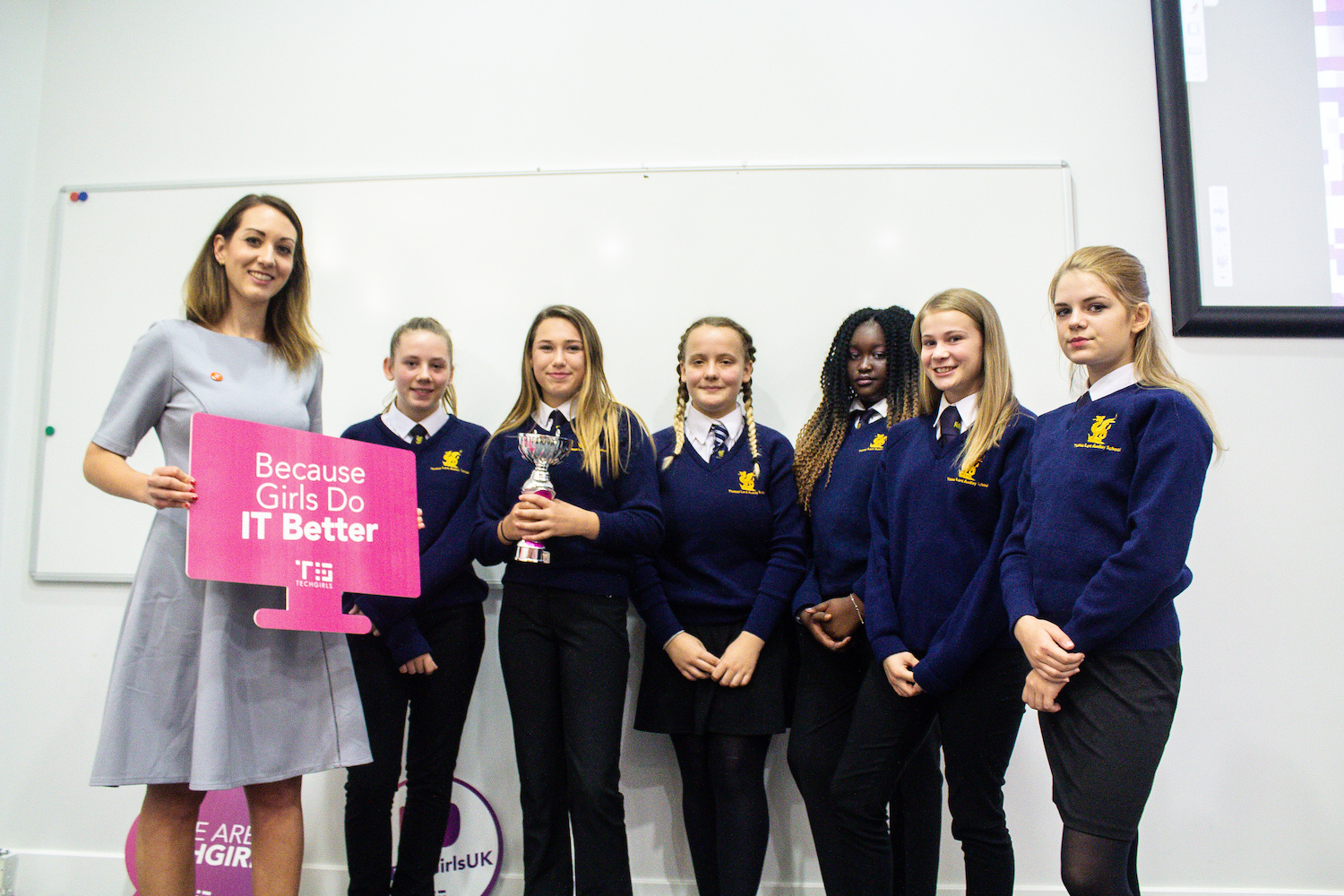 Professional Photography Six Female Students In Blue Sweatshirts Holding Silver And Pink Trophy At Event With Woman In Grey Dress
